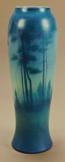 Thrown refined white stoneware body of tapering cylindrical form, flaring to circular foot.  Decorated underglaze with trees and landscape, shaded predominantly in dark green and blue. Transparent matte glaze.