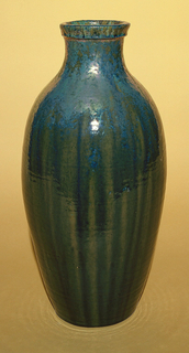 Buff clay body, thrown.  Ovoid body with incurving neck and molded rim; no foot.  Allover thick blue-green high glaze with striations of yellow-green.  Gold and purple luster iridescence at shoulder and neck.  Interior glazed.  Slight clazing to glaze.  Glaze very thick on bottom.