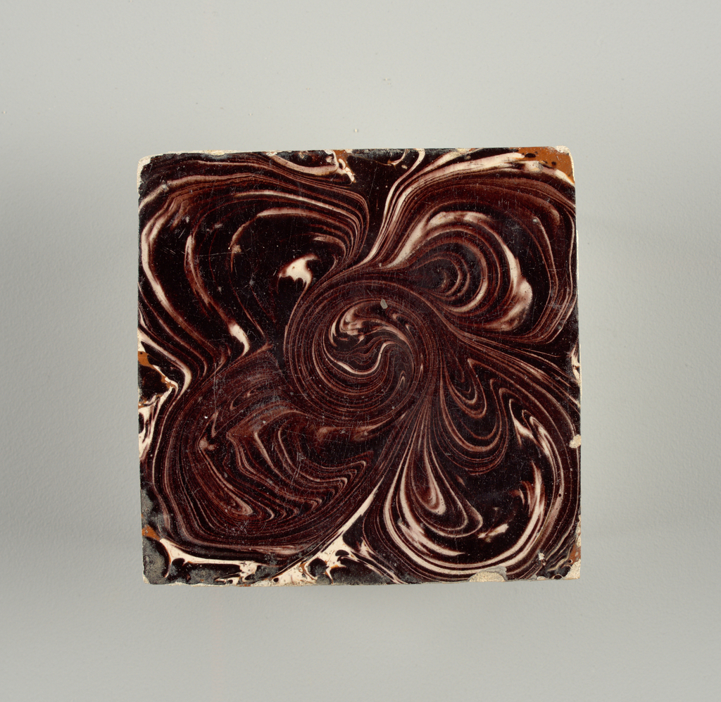 Square tile, surface painted with underglaze manganese purple in swirled pattern. Clear glaze (kwaart) over tin glaze.