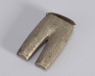 A silver colored matchsafe in the form of pants with a circular lid on top.
