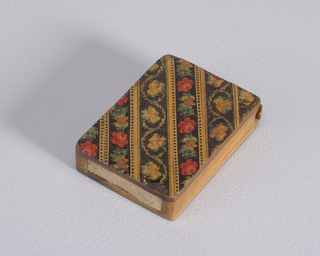 Rectangular, with rounded corners, featuring alternating diagonal stripes of stylized flowers and continuous leaf design, rendered in stained wood mosaic work. Reverse features only the continuous leaf motif, as seen on front. Colors are red, green, blue, medium and dark brown on black background. Side panels and lid are plain, unstained wood. Flat, thin lid recessed and hinged on pin in top portion of box. Striker of sandpaper recessed in bottom.