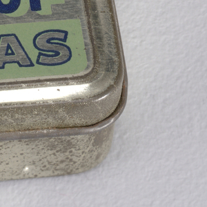 "Rectangular, rounded corners, silver colored tin, the lid printed ""BELL'S WATERPROOF WAX VESTAS"" in alternating colors of blue, green and silver. Lid hinged on back. Striker on bottom."