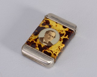 Retangular metal form wrapped in sheet of celluloid immitating tortoishsell; recto with circular portrait photograph of William Jennings Bryan; hinged flip-top; striker on bottom.
