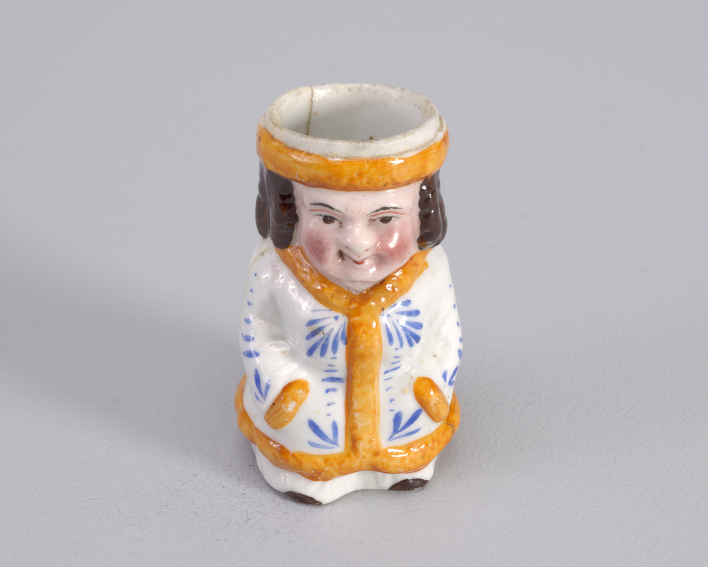 Figure of man in white dressing gown with orange trim and blue foliate design.