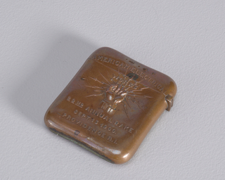 "Rectangular, curved sides and corners, each side slightly cinched at center, featuring raised decoration of clenched hand with lightning bolts radiating from within, inscribed above ""American Electrical"" and below ""22nd Annual Bake, Sept. 13, 1900, Providence, R.I."" Lid hinged on side. Striker on bottom."