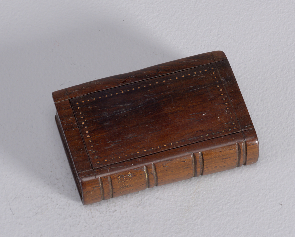 A dark wood matchsafe in the form of an old book.