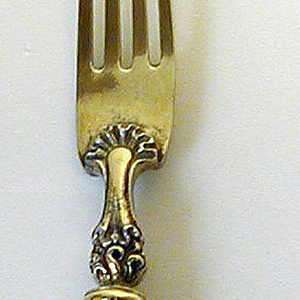 Four-tined fork, tines slightly curved and tapering towards the point. Gilded join and baluster-shaped neck decorated with scallops, scrolls and stylized lion's head on the back of the join. Gilded ferrule ribbed, round in section. Tapering white porcelain handle with multi-color decoration of flowers and birds, and two scenes surrounded with gilded scrolled decoration: on the front, a harbor scene with two men raising their glass, on the back a landscape with a lady and a small girl holding a doll.
