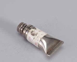 A silver colored matchsafe in the form of a paint tube with a worn white label.