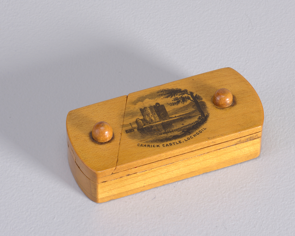 "Oblong, with short sides curved. ""Pencil Box"" type construction with 3 interlocking parts that swivel open on wooden pins. The first or upper layer features a black, transfer printed image of a castle in bucolic setting, inscribed ""CARRICK CASTLE, LOCHGOIL"" below. When uppermost layer is pivoted open, a coin-size, circular recess is revealed, possibly the area on which the match was struck; this second section or layer, when opened, reveals main body hollowed out for containing matches."