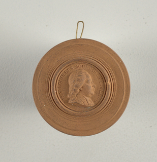 """Circular, with wide moulded border. Bust in relief of middle-aged man, in profile to right. Inner border inscribed in relief: """"AIME LOUIS DES MOULINS DE LISLE. 1770""""."""