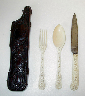Leaf-shaped blade, slightly hollow in the centre, plain bolster. Pistol- shaped carved ivory handle with floral decoration and a decorative pattern with leaves, beads and scrolls following the contours of the handle.