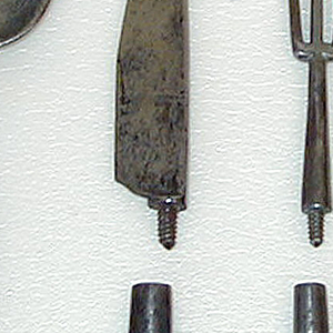 Small case for six implements, stamped leather with scrolled decoration in gold. Case consists of two parts, body and lid, held together with a cord.