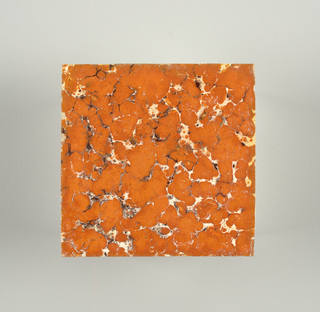 Square tile, painted with underglaze random pattern of red-orange and black spots, simulating stone. Clear glaze (kwaart) over tin-glaze and underglaze colors.