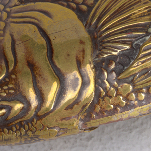 In the shape of a fish with raised decoration of scales, gils, fins, with tail folded over one side of body, slight patina all over. Head flips open, hinged on top. Scales likely intended as striker.