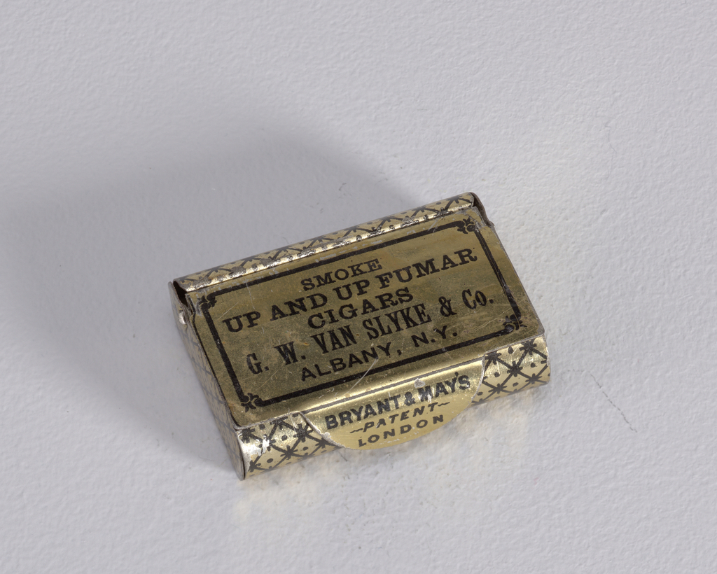 """Rectangular, curved sides, snuff box style container, featuring black printed decoration on gold ground, cover inscribed """"Smoke Up and Up Fumar Cigars, G.W. Van Slyke & Co., Albany, N.Y."""", inscribed on thumb catch to right """"Bryant & May's, Patent, London"""" , diamond, star and dot pattern on rest of box body. Striker on reverse."""
