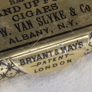"Rectangular, curved sides, snuff box style container, featuring black printed decoration on gold ground, cover inscribed ""Smoke Up and Up Fumar Cigars, G.W. Van Slyke & Co., Albany, N.Y."", inscribed on thumb catch to right ""Bryant & May's, Patent, London"" , diamond, star and dot pattern on rest of box body. Striker on reverse."