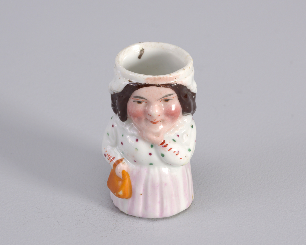 Figure of woman in dress with lavender skirt and white ruffled top with dark green and rust dots. Figure holds left hand to chin and an orange bag in right hand.