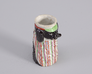 Figure of dog wearing white bib with red and green patterned stripes aqnd cap with white, green and orange parts.