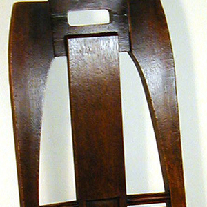 Trapezoidal, caned slip seat tapered toward back; four tapered legs of square section, swelling toward foot; paired struts on back and sides; chair back with tapered curved sides, central vertical splat with rectangular depression, surmounted by pierced horizontal rectangular section. Caning on seat not original.