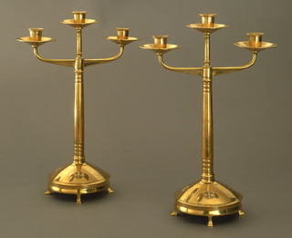 Three-arm candelabrum on circular base with folded, molded foot pads. Base domed; three circular motifs with central cross and central bead on upper surface of base, front and sides. Fourth motif contains maker's monogram. Tapered molded shaft with socket and cup at upper end, flanked by pair of molded arms, each with candle socket.