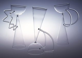 "Double reversible wine glass of clear blown glass. Elongated conical flutejoined at point to hemispherical bowl positioned at angle. Two applied glass ""handles"" at side in ""C"" shape connect flute to bowl."