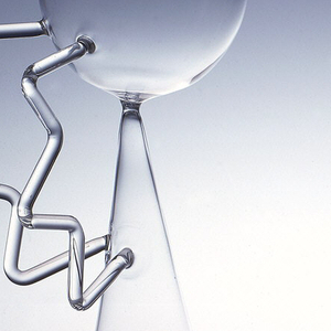 """Double reversible wine glass of clear blown glass. Elongated conical flute joined at point to hemispherical bowl positioned at angle. Two applied glass """"handles"""" at side connect flute to bowl, curved at juncture with flute and horizontal to parallel lip of the bowl."""