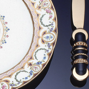 Gilt bronze spoon with black handle decorated with four gilt rings, terminating at flat gilt disc.