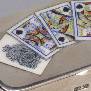 Oblong, with curved corners, snuff box type container featuring polychrome decoration of a fanned hand of playing cards: from left, first card is ace of spades in black and white enamel, followed by king of spades, queen of spades, jack of spades, all in red, blue, yellow, black, white enamel, ace of hearts in red and white enamel. Underside of box features elaborate monogram (AE). Lid hinged on back panel. Striker on right panel.