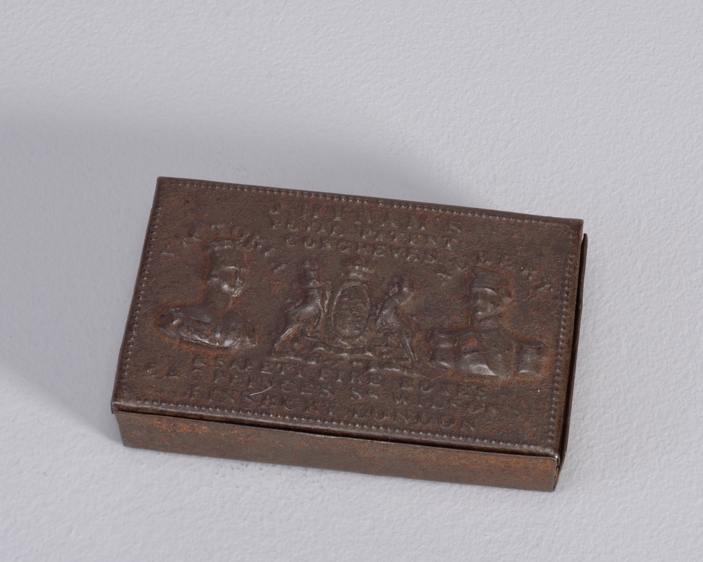 """Rectangular, snuff box style container, featuring raised decoration of Queen Victoria and Prince Albert, their names inscribed above each respectively, royal coat-of-arms between them, inscribed above all """"J.Hynam's Royal Patent Congreves,"""" inscribed below """"& Safety Fire Boxes, 5 & 7 Princes Sq. Wilson St., Finsbury London."""" Lid hinged on back, long side. Striker on same side."""