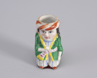 Figure of man wearing Near Eastern costume with green jacket with yellow collar and tied with white belt and red stripes and white outfit underneath with light blue stripes. Figure wears white turban with diagonal rust stripes.