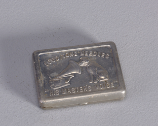 "Rectangular, snuff box style container, featuring raised decoration of seated terrier dog peering into gramaphone speaker, inscribed above ""Loud Tone Needles"" and below "" 'His Master's Voice' "". Striker on underside."