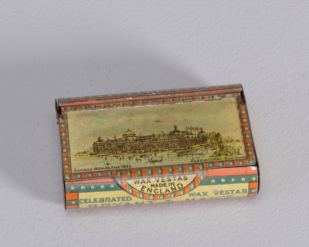 "Rectangular, long sides curved, snuff box style container, featuring cover with polychrome printed decoration of very large fair building, inscribed below ""Chicago World's Fair 1893, Agricultural Building,"" thumb catch on cover inscribed ""Wax Vestas Made in England,"" inscribed on curved front panel ""Celebrated Wax Vestas, Bryant & May's,"" inscription identical on reverse curved panel with order reversed, short sides both inscribed ""Bryant & May London""; all inscribed reserves framed by alternating blue and red bands, with stars punctuating all the blue bands. Cover hinged on reverse curved panel. Striker on underside of box."
