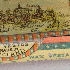 """Rectangular, long sides curved, snuff box style container, featuring cover with polychrome printed decoration of very large fair building, inscribed below """"Chicago World's Fair 1893, Agricultural Building,"""" thumb catch on cover inscribed """"Wax Vestas Made in England,"""" inscribed on curved front panel """"Celebrated Wax Vestas, Bryant & May's,"""" inscription identical on reverse curved panel with order reversed, short sides both inscribed """"Bryant & May London""""; all inscribed reserves framed by alternating blue and red bands, with stars punctuating all the blue bands. Cover hinged on reverse curved panel. Striker on underside of box."""