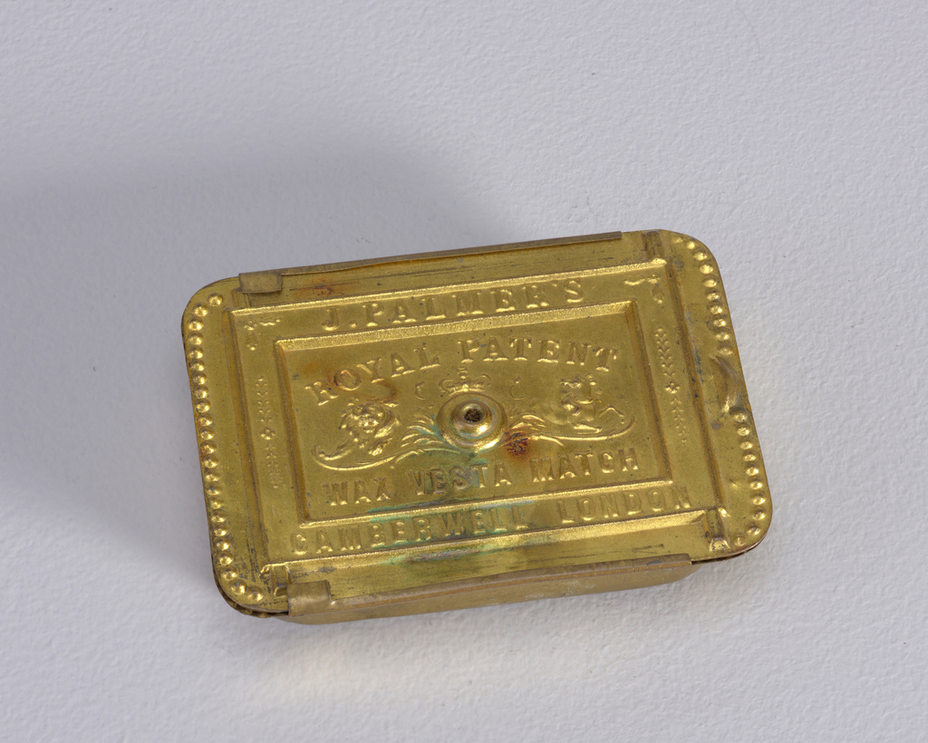 "Rectangular, curved corners, canted sides, with cover that slides off top of box; cover features beading on right and left edges, with thumb catch on right side, raised frame contains inscription ""J. Palmer's, Camberwell London""; inscription inside frame reads ""Royal Patent, Wax Vesta Match""; at center is small raised opening to hold single lit match, to left is image of lion, over opening is crown, to right is image of a horse; underside inscribed ""Alexander S. Stocker, Patentee"" in upper recessed area, striker in central recess, ""Brass Battery Works, Wandsworth Surrey"" inscribed in bottom recess."