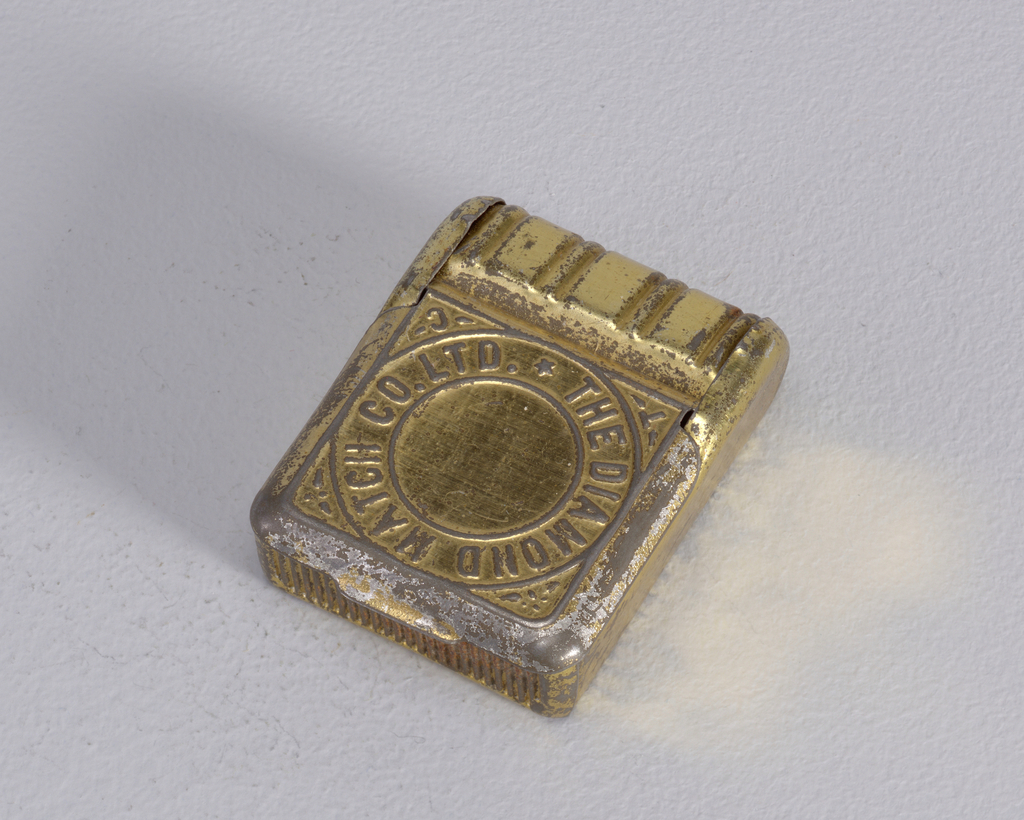"Rectangular, upper part curved with bands that run from front to back, cover opens on front, thumb catch at bottom, cover inscribed in a circle ""The Diamond Match Co. Ltd."", ""T"" and ""C"" inscribed on corners outside of circle. Striker on bottom beneath thumb catch."