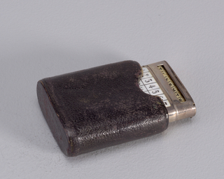 "Rectangular, with rounded edges, featuring white enameled reserve with black enameled calender numbers, 1 through 31. Above, on lid front, is open window through which a rotating, adjustable, 7-sided, bone rod with first letters of the days of the week may be viewed. Lid opens in two opposite places; its thin, flat top hinged on upper right; when flipped up, compartment containing adjustable bone rod is revealed. Lid hinged again on upper left, below open window, and above calender, accessing match container. Reverse features inscription ""Manchester Ship Canal, Opening for Traffic, Souvenir, Cunard SS Skirmisher, 1st Jan.y 1894, J.D. Macgregor"". Striker on bottom. Seperate black leather case lined in blue velvet."