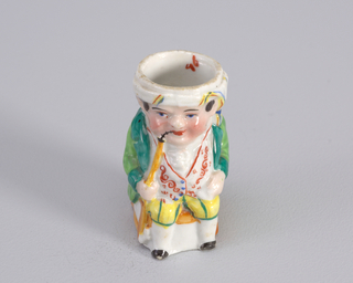 Figure of man seated wearing Near Eastern outfit with green coat, short yellow pants with green stripes and white waistcoat with red decoration and light blue buttons. Figure smokes a long narrow orange colored pipe. Figure wears a turban on head.