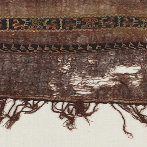 One end of a loosely woven plain weave wool fabric with tapestry woven bands at one one. One band derived from Arabic script in black and ivory. The wider band a repeat of units containing two birds and a polychrome geometric band. The wider band reserved in the dying of the fabric to produce a deep red. Warp fringe at bottom.