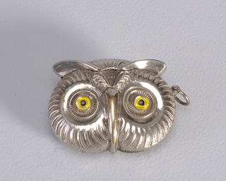 In the form of an owl's head, with stylized feathers on front and reverse, long narrow beak, yellow glass eyes. Top of head to upright, tufted feathers above brow line, serves as lid. Lid hinged on reverse. Link attached to upper right side. Striker on bottom.