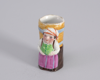 Figure of woman wearing pink skirt, lime green bib and kierchief with red stripes. Figure standing in front of barrel.
