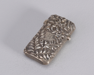"Oblong, rounded sides and corners, featuring over-all repoussé floral decoration on stippled ground; reverse features some variation in floral decoration with monogram ""EM"" engraved in small, open, central reserve. Small protruding button on side opens lid when depressed; lid hinged on opposite side. Striker on bottom."