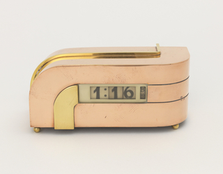 Rectangular form with curved sides composed of copper bands flanking a central brass band; narrow, curved and angled decorative brass strip runs along surface of top and left side;central dial consisting of black roman numerals on rotating white plastic wheels; four small ball feet.