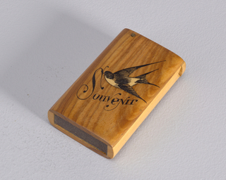 "Oblong, vertical sides curved, with image of a swallow in flight, rendered in inlaid woods and black paint, under which is the inscribed word ""Souvenir"" in black. Inscribed in black on reverse is ""Nice."" Simple flat lid, attached to metal pin, hinged on left side. Striker of sandpaper is recessed into bottom of box."