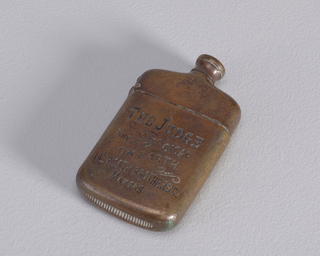 "A copper colored matchsafe in the form of a bottle. The front says"" The Judge Finest 5c Cigar on earth Dilworth Brothers co. Makers"""