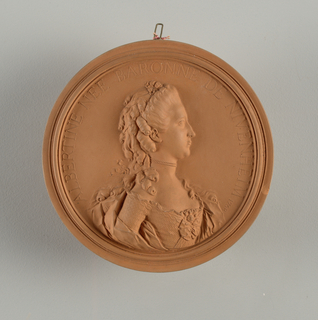 """Circular. Bust of young lady in high relief; half-right, head in profile. Hair dressed with ribbons and curls. Pearl necklace. Embroidered robe, square decollete, with bow knots and rose. Circular border inscribed in relief: """"ALBERTINE NEE BARONNE DE NIVENHEIM 1768""""."""