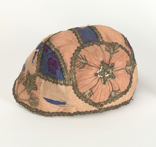 Child's cap made up of strips of pink silk moiré ribbon with three small insertions of purple and blue brocaded silk over the crown. Outlined with narrow silver lace. Floral sprays in center back and each front corner and embroidered with silver sequins and fine silver wire. Lined with white cotton. Chin ribbons of blue silk moiré. Machine-made lace facing.