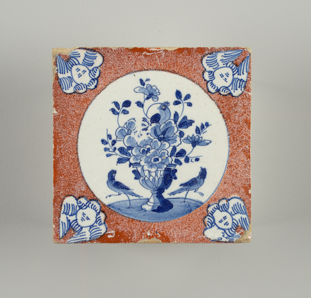Square tile. Centered with circular medallion enclosing a vase with flowers and two addorsed birds, blue on white. Border of powdered orange-red, with blue on white cherubs' heads at the corners. In black walnut frame.