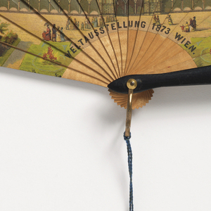 Brisé fan with pierced wood sticks, threaded with blue silk ribbon and with a blue silk tassel.  On the obverse, a chromolithograph is pasted onto the sticks.