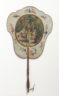 "Handscreen with a paper leaf and turned wood handle. Obverse: oval medallion with a hand-colored engraving showing two couples eating a meal in a landscape, surrounded by a border of hand-painted musical instruments. Reverse: printed with dialogue from the comic opera ""Les Solitaires de Normandie."""