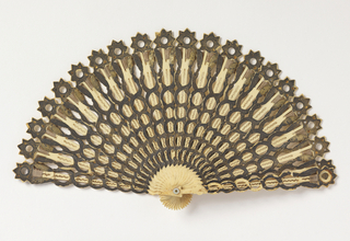 Brisé fan with star and leaf pattern. Sticks of incised and drilled bone decorated with metallic foil and polished steel spangles; silk connecting ribbon; mother-of-pearl washer at the rivet.